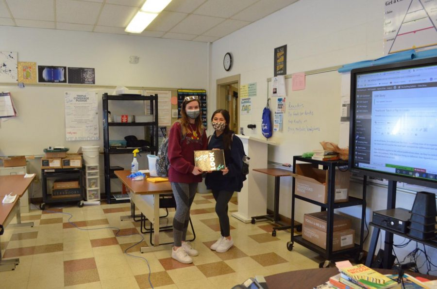 Senior yearbook staff members Mara Crish and Marianna Franco show off the 1994 Epic - the inspiration for the 2021 Epic